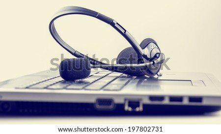 Retro image of black headset on laptop keyboard. Conceptual of customer support or online chat, discussion or conference. - stock photo