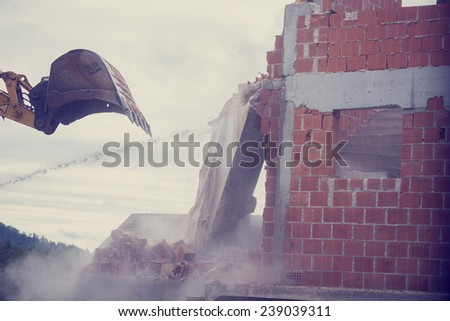 Retro image of bucket of a backhoe or mechanical digger demolishing the wall of a brick building with flying masonry and debris. - stock photo