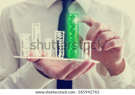 Retro image of businessman holding a hand-drawn bar graph in his hand with a single elevated green bar which he is touching and activating with his finger as though on a virtual computer interface. - stock photo