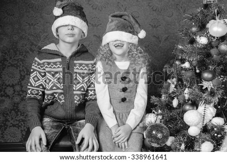 Retro image of funny kids with Santa hats at Christmas holiday near decorated christmas tree. New Year. Concept of family celebration. Retro revival, old edition, black and white - stock photo