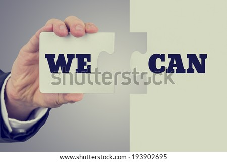 Retro image of male hand  holding words We can  split over two puzzle pieces. Conceptual of determination, willpower and belief.  - stock photo