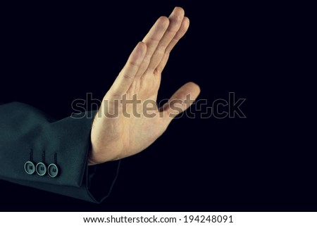 Retro image of man in a suit raising his hand in a stop gesture showing he has had enough or calling a halt or fending off something or someone against a dark background with copyspace. - stock photo