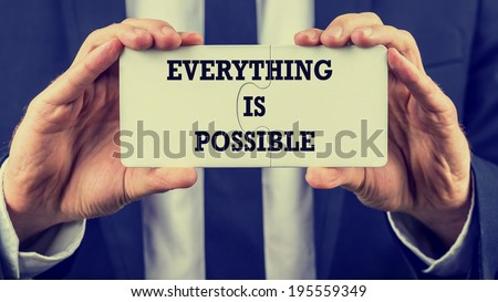 Retro instagram style image of a businessman holding two joined jigsaw puzzle pieces with phrase - Everything is possible - conceptual of optimism and determination. - stock photo