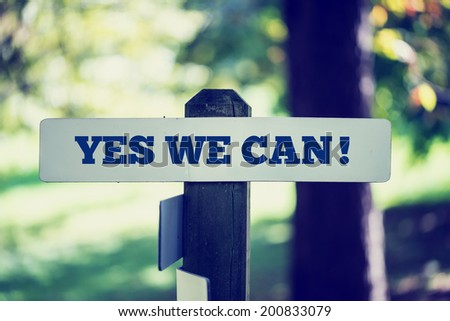 Retro instagram style image of an old rustic signpost with the phrase Yes we can, outdoors in sunny woodland. - stock photo