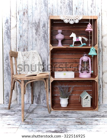 Retro interior with chair and  three wooden  crates with different home related objects on wooden wall background