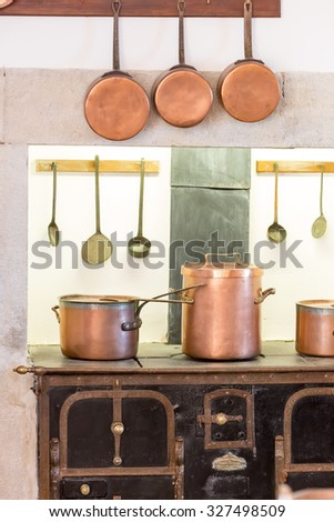 Retro kitchen interior with old pans, pot on the furnace - stock photo