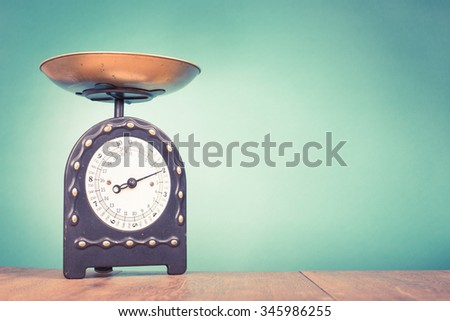 Retro kitchen weight measurement balance on table. Old style filtered photo - stock photo