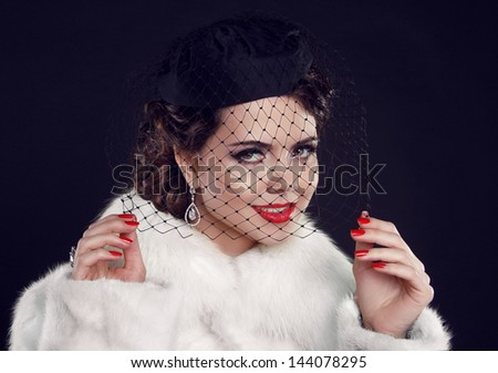 Retro lady with hat. Beautiful Woman in Luxury Fur Coat.  Fashion model Isolated on dark background.