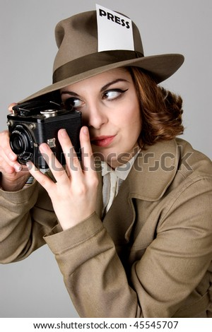 Retro looking woman holding a vintage camera. - stock photo