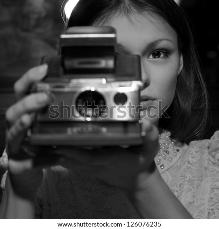 Retro looking young beautiful woman holding a vintage retro camera. - stock photo