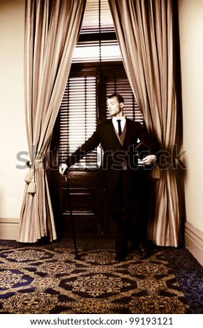 Retro male servant standing guard at a curtained entranceway holding his masters cane and tophat while he waits patiently to be of service - stock photo