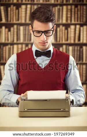 Retro man in vintage clothes, writing a novel at a typewriter. - stock photo