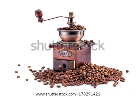 Retro manual coffee mill on roasted coffee beans isolated - stock photo