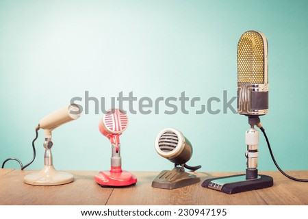 Retro mass media microphones for broadcasting or recording front mint green wall background - stock photo