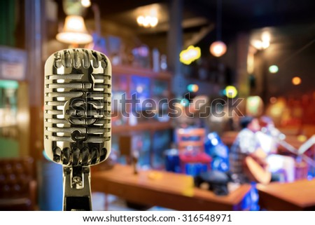 Retro microphone against blur colorful light in pub and restaurant background - stock photo