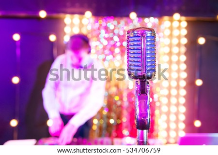 Retro Microphone and DJ on the blurred background, in a room there are festive bulbs