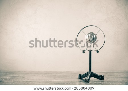 Retro microphone from 50s on wooden table. Vintage old style sepia photo - stock photo
