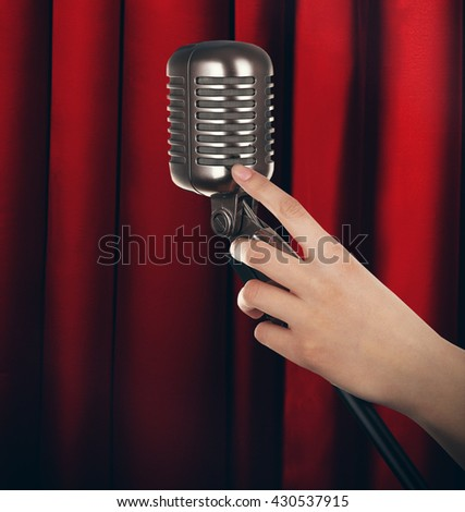 Retro microphone in female hand on red curtain background