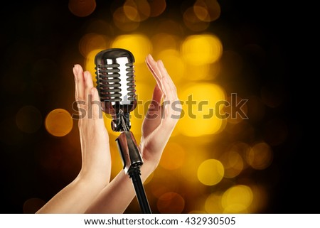 Retro microphone in female hands on abstract blurred background