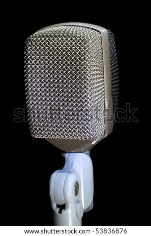 Retro Microphone on stand with black background.