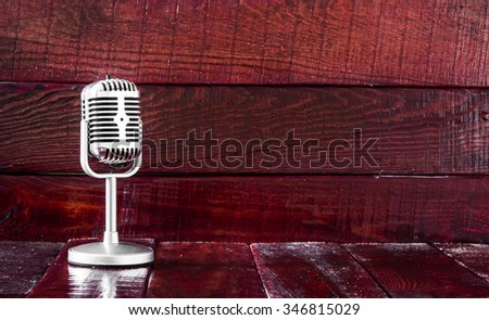Retro microphone on wooden table - stock photo