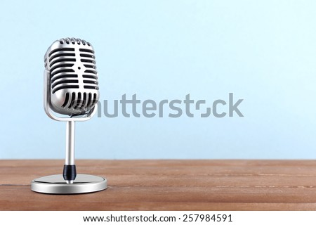 Retro microphone on wooden table on light background - stock photo