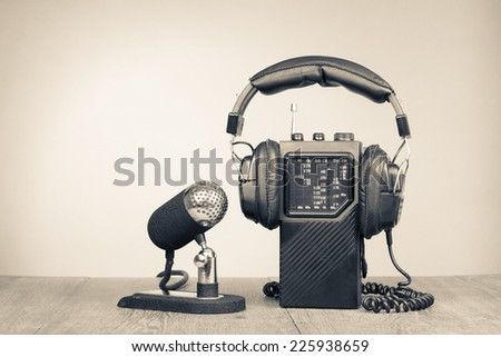 Retro microphone, portable radio and headphones on table. Vintage old style sepia photo - stock photo