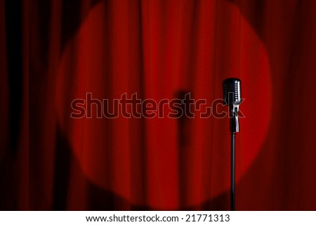 Retro microphone with a red curtain background - stock photo