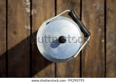 retro milk can with wooden background - top view - stock photo