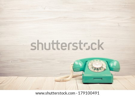 Retro mint green telephone on wooden table - stock photo