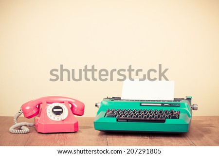 Retro mint green typewriter and pink rotary telephone on table - stock photo