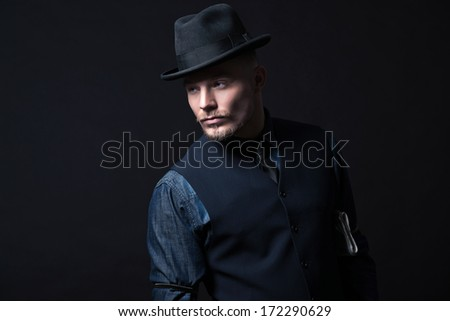 Retro 1900 modern fashion man. Wearing blue jeans shirt with gilet and trousers. Black hat. Studio shot against black. - stock photo