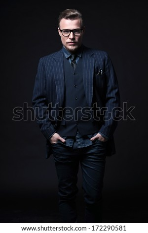 Retro 1900 modern fashion man with blonde hair and beard. Wearing blue striped suit and black glasses. Studio shot against black. - stock photo