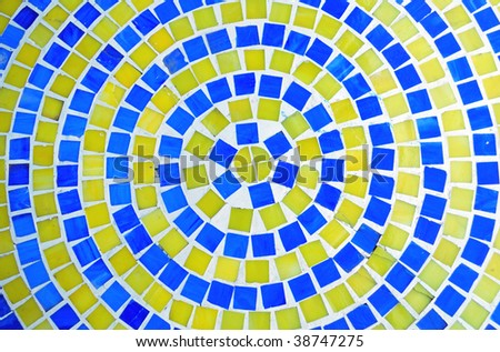 Retro Mosaic in a circular pattern of blue and yellow tiles. - stock photo