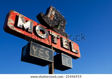 retro motel sign - abandoned motel against clear blue sky - stock photo