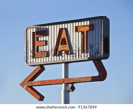 Retro neon eat sign ruin in early morning light. - stock photo