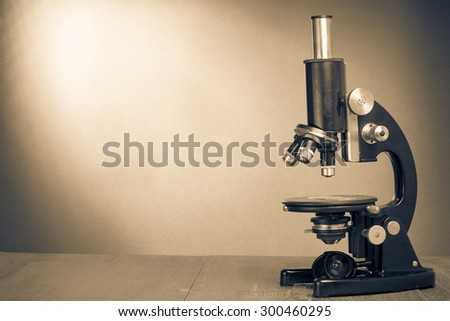 Retro old microscope on table. Vintage style sepia photo - stock photo