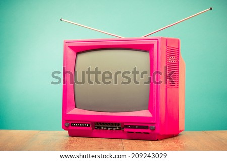 Retro old pink television front mint green background - stock photo