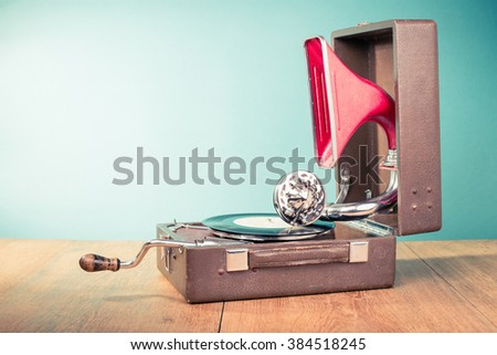 Retro old portable phonograph front mint green background. Vintage style filtered photo - stock photo