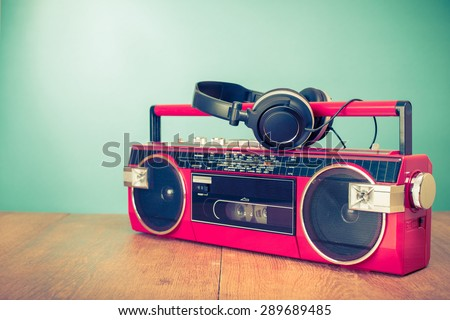 Retro old radio cassette tape recorder from 80s and headphones front mint green background. Vintage instagram style filtered photo - stock photo