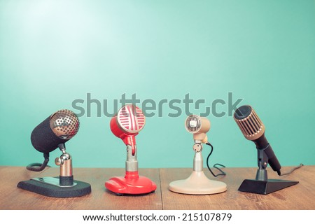 Retro old style microphones for press conference or interview front mint green background - stock photo