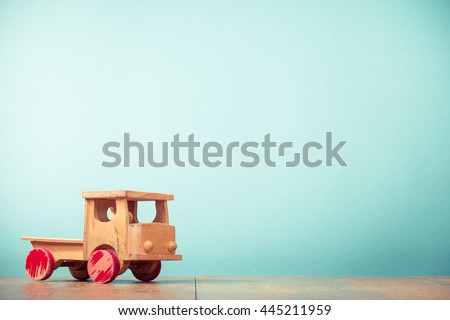 Retro old toy wooden truck front aquamarine background. Vintage instagram style filtered photo - stock photo