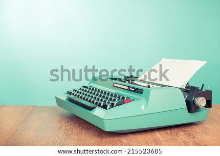 Retro old typewriter with paper on wooden table front mint green background - stock photo