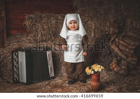 Retro! One year smiling baby with accordion dressed in Second World War nurse russian uniform. Hay background.  - stock photo