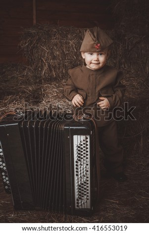 Retro! One year smiling baby with accordion dressed in Second World War russian uniform.  Hay background. - stock photo