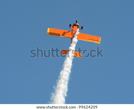 retro orange colored airplane performing aerobatics - stock photo