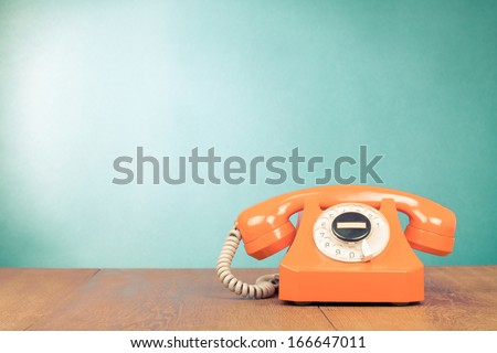 Retro orange telephone on table front mint green wall background - stock photo