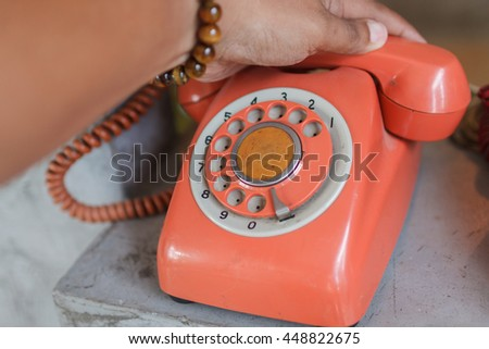 Retro orange telephone on wood table and hand - stock photo