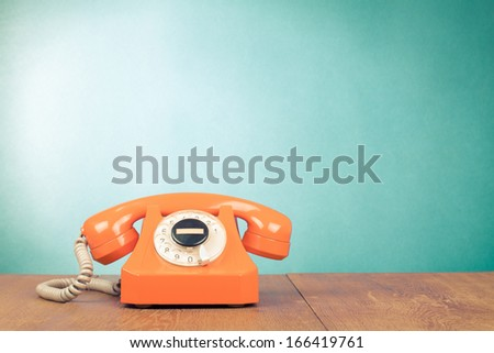 Retro orange telephone on wood table near aquamarine wall background - stock photo