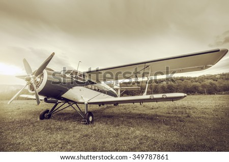 Retro passenger plane stands on the meadow before the flight. - stock photo